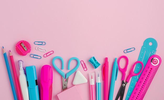 Forniture scolastiche colorate su sfondo rosa.