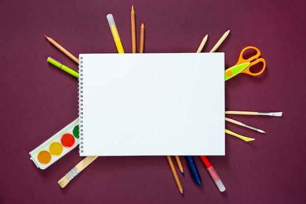 Forniture scolastiche su uno sfondo viola