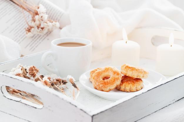Forno dolce con la tazza di caffè con latte sul vassoio elegante misero di legno bianco con le candele e il libro brucianti.