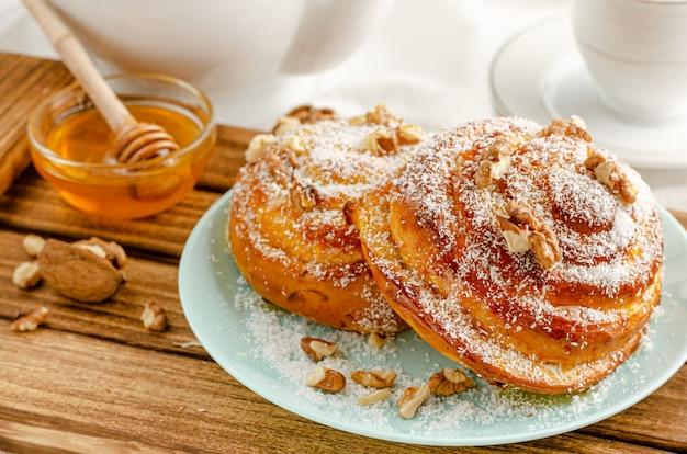 Forno svedese tradizionale o kanelbulle con le noci sul vassoio di legno. concetto di colazione o merenda. avvicinamento