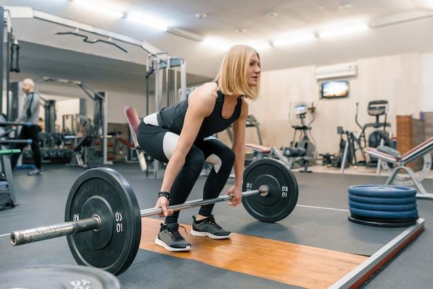 Forte allenamento donna adulta con pesi pesanti in palestra