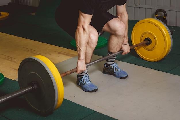 Forte atleta crossfit in un sollevamento pesante e tozzo in una palestra di boxe cross-fit