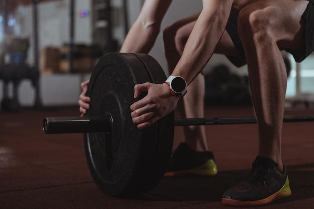 Forte atleta maschio crossfit che si esercita con bilanciere pesante