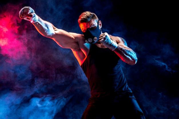 Forte atleta maschio in una maschera nera da allenamento su una parete nera