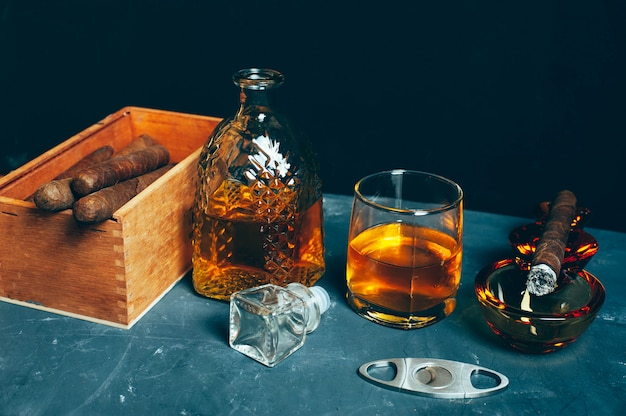 Forte bevanda alcolica, whisky scozzese in vetro e decanter con sigaro fumante nel posacenere