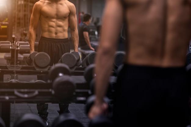 Forte bodybuilder atletico fitness uomo pompando i muscoli addominali