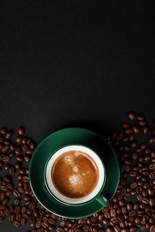 Forte caffè nero in una tazza di colore verde smeraldo su uno sfondo nero opaco