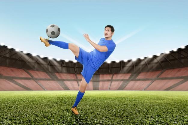 Forte calciatore asiatico calcia la palla