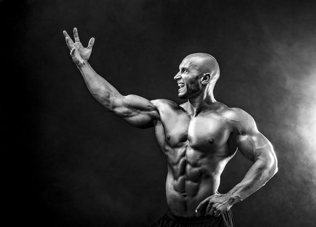 Forte culturista che posa e che mostra i muscoli