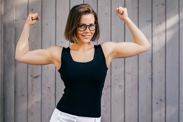 Forte donna fitness con i capelli corti vestita casual, dimostra il suo bicipite all'aperto