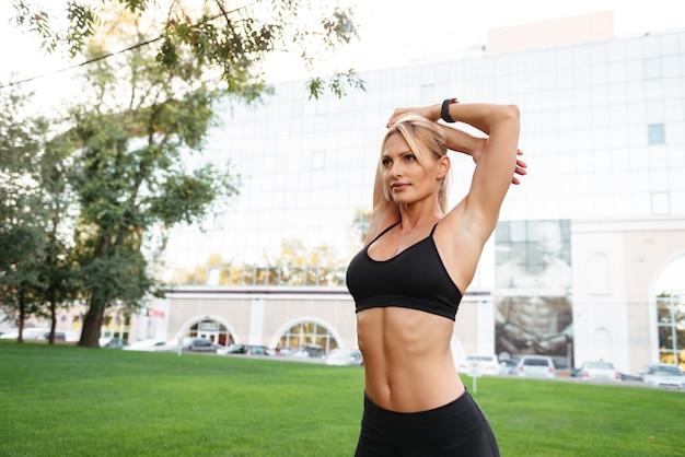 Forte giovane donna sportiva in piedi all'aperto