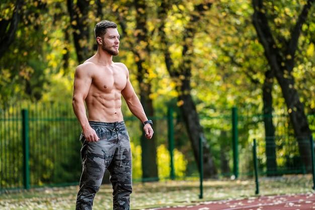 Forte lavoro maschile, fitness all'aperto. sollevamento di attrezzi pesanti. sportivo bello. giovane culturista. atleta mezzo nudo. bel corpo. uomo bruna.