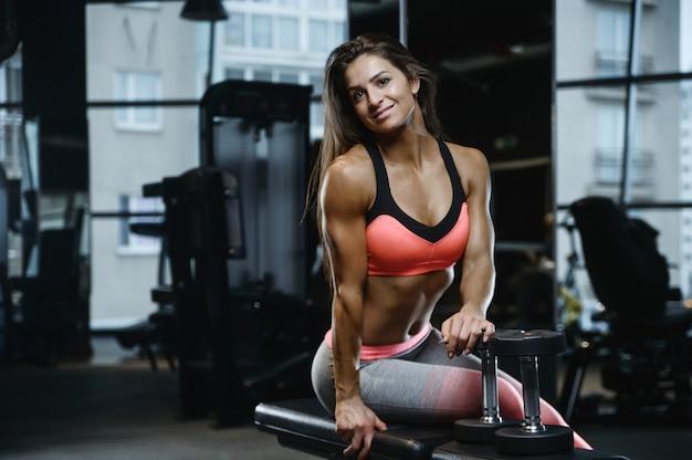Forte ragazza atletica sexy che risolve in palestra