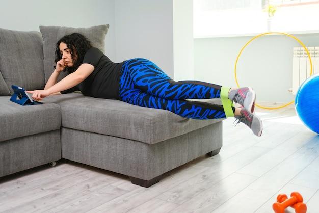 Forte ragazza sportiva in abiti sportivi. esercizio di fitness. ragazza che guarda tutorial online su tablet.