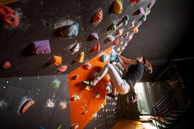 Forte scalatore femminile sulla parete rampicante del masso dell'interno