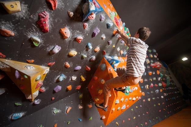 Forte scalatore maschio sulla parete rampicante del masso dell'interno