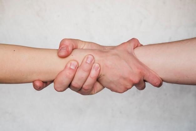 Forte stretta di mano su sfondo bianco