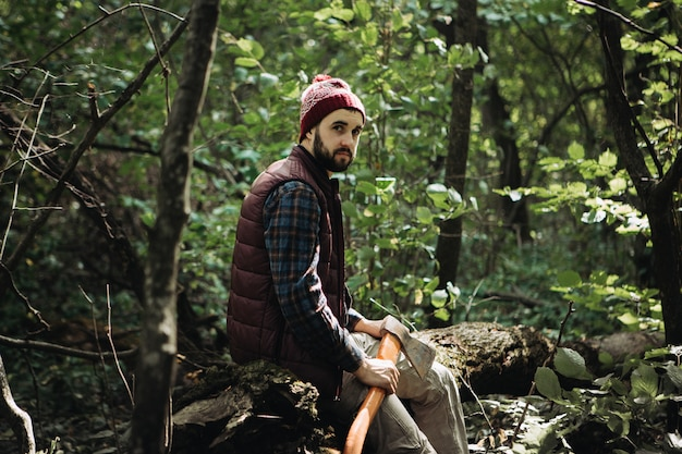 Forte taglialegna barbuto con un'ascia nel bosco