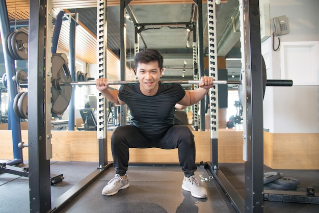 Forte uomo asiatico in piedi e bilanciere di sollevamento in palestra