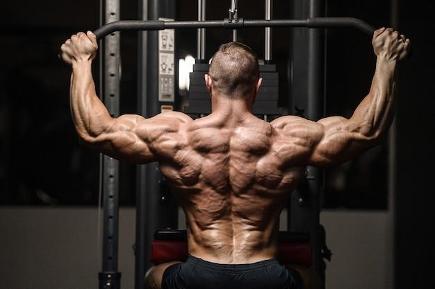 Forte uomo atletico pompare i muscoli della schiena