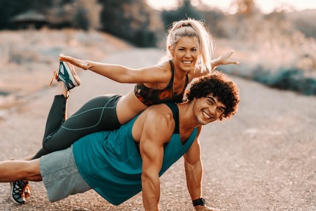 Forte uomo caucasico con i capelli ricci con la sua ragazza sulla schiena mentre si fa push up. esercizio nel concetto di natura.