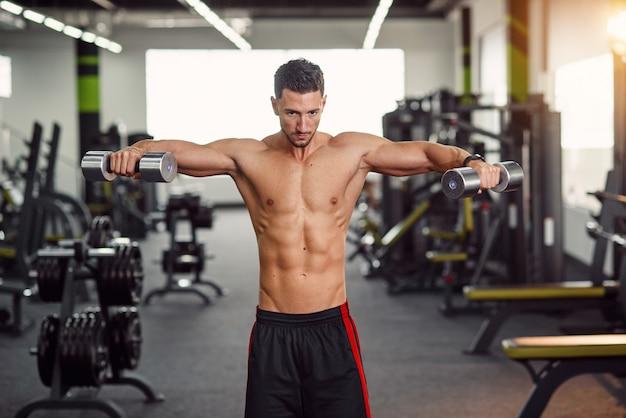 Forte uomo in buona salute allenando le spalle in palestra. esercizio isolato per l'allenamento del muscolo deltoide. allenati nella moderna palestra .;