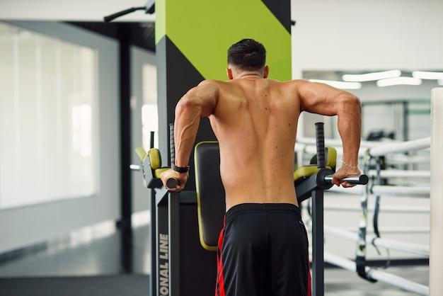 Forte uomo in buona salute facendo flessioni su barre parallele durante l'allenamento in palestra moderna. vista posteriore. concetto sportivo e sano.