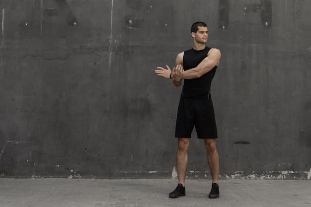 Forte uomo muscoloso, sportivo che si scalda, si prepara per l'allenamento