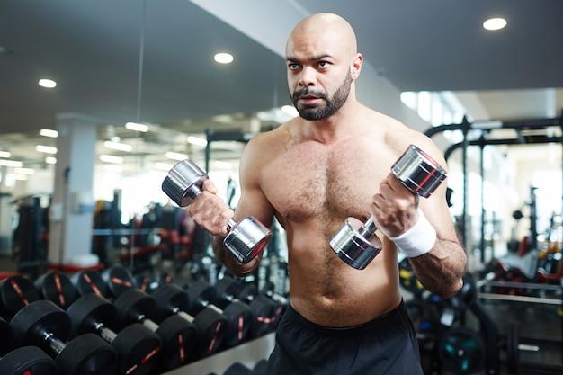 Forte uomo senza camicia che risolve con i pesi