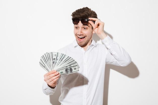 Fortunato uomo in camicia togliendosi gli occhiali da sole neri e godendo fan di soldi banconote da un dollaro con eccitazione e sorriso, isolato su un muro bianco con ombra