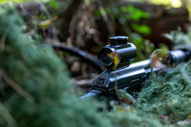 Forze speciali, fucile d'assalto soldato con silenziatore, mirino ottico. dietro copertura in agguato