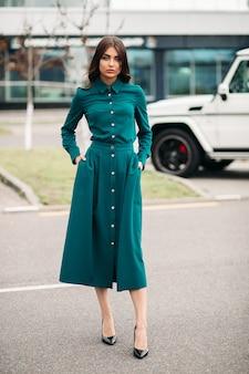 Foto a figura intera della splendida signora in abito verde in piedi all'aperto mentre posa alla macchina fotografica. stile e concetto di moda