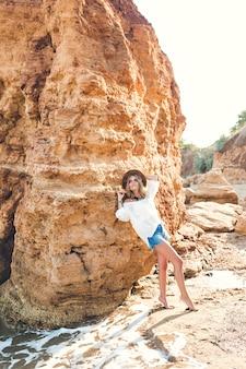 Foto a figura intera di bella ragazza bionda con i capelli lunghi in posa per la fotocamera sulla spiaggia su sfondo di roccia.