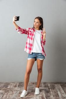 Foto a figura intera di giovane bella donna, che prende la foto del selfie dai suoi telefoni