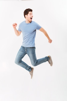Foto a figura intera di uomo spaventato teso 30s in t-shirt casual e jeans scappando in studio, isolato sul muro bianco