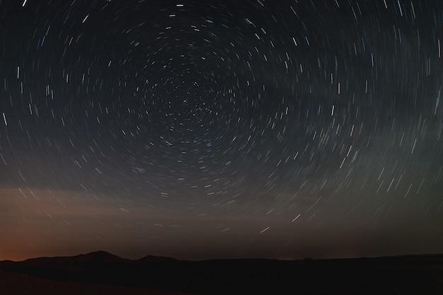 Foto a lunga esposizione del cielo nel deserto del sahara, guardando tracce di stelle di notte.
