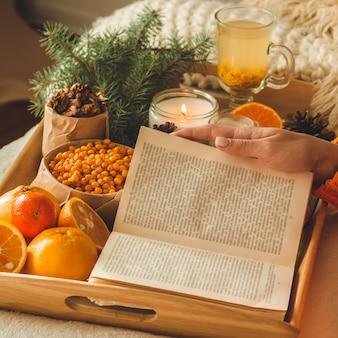 Foto accogliente e morbida di donna in caldo maglione arancione sul letto con una tazza di tè e libro.