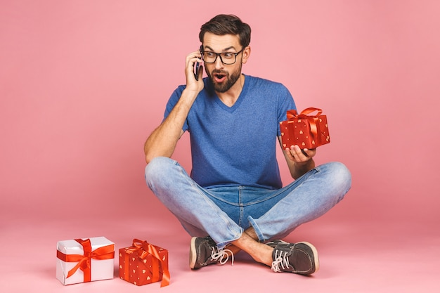 Foto adorabile del giovane attraente con le belle scatole del regalo di compleanno della tenuta di sorriso isolate sopra la parete rosa, sedentesi sul pavimento. concetto di regalo. usando il telefono.