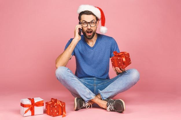 Foto adorabile del giovane attraente in cappello di natale con il bello sorriso che tiene le scatole del regalo di compleanno isolate sopra la parete rosa, sedentesi sul pavimento. concetto di regalo. usando il telefono.