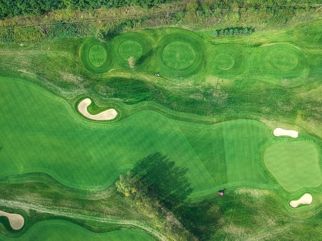 Foto aeree di mazze da golf, prati verdi, boschi, tosaerba, posa piatta
