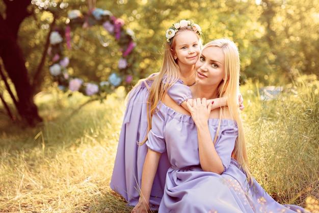 Foto all'aperto di moda di bello aspetto familiare. bella madre con lunghi capelli scuri in posa con il suo piccolo bambino carino in abiti simili con stampa di fiori