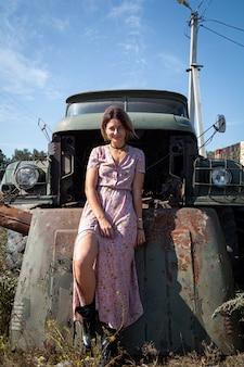 Foto all'aperto di stile di vita atmosferico del ritratto di giovane bella donna dai capelli scuri in un vestito rosa in una stampa floreale sullo sfondo di una vecchia automobile del camion. concetto di autunno a piedi