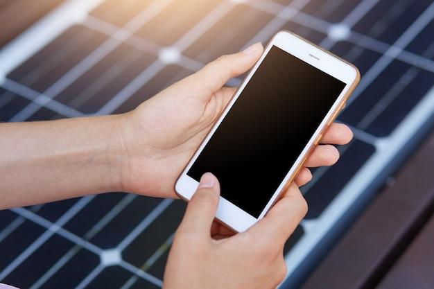 Foto all'aperto di una persona senza volto che danneggia il telefono cellulare tramite usb. carica pubblica sulla panchina con pannello solare sulla strada della città