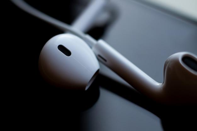 Foto astratta delle cuffie sul vetro di un primo piano dello smartphone. tecnologia, design ed ergonomia.