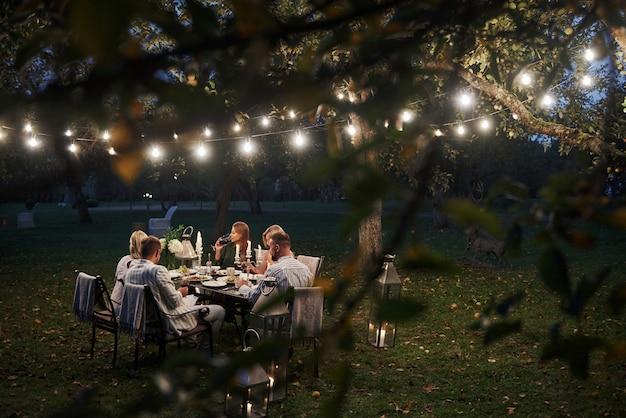 Foto attraverso i rami degli alberi con foglie. tempo di sera. gli amici cenano nello splendido posto all'aperto