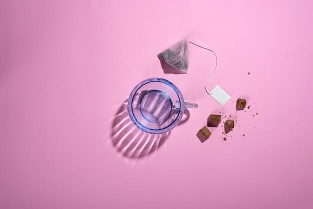 Foto creativa con una tazza di vetro blu con belle ombre riflettenti, un sacchetto di tè