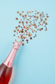 Foto creativa della bottiglia di champagne con confetti