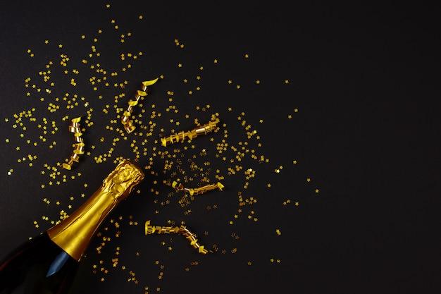 Foto creativa di concetto della bottiglia del champagne con i coriandoli della stella