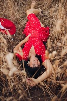 Foto d'archivio dall'alto di una splendida giovane donna dai capelli scuri in abito rosso a pois e tacchi sorridendo alla telecamera mentre ci si rilassa a terra nel campo di grano.