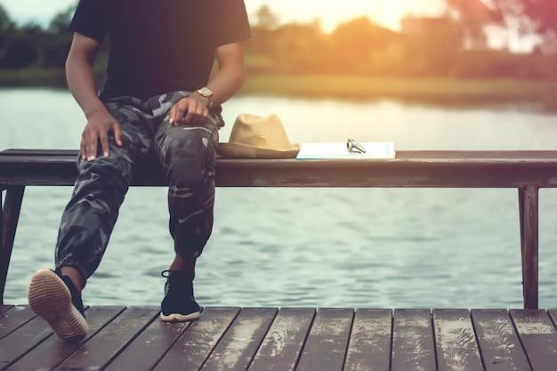 Foto d'epoca di uomo rilassante con godersi l'aria fresca sul balcone di legno dal fiume.